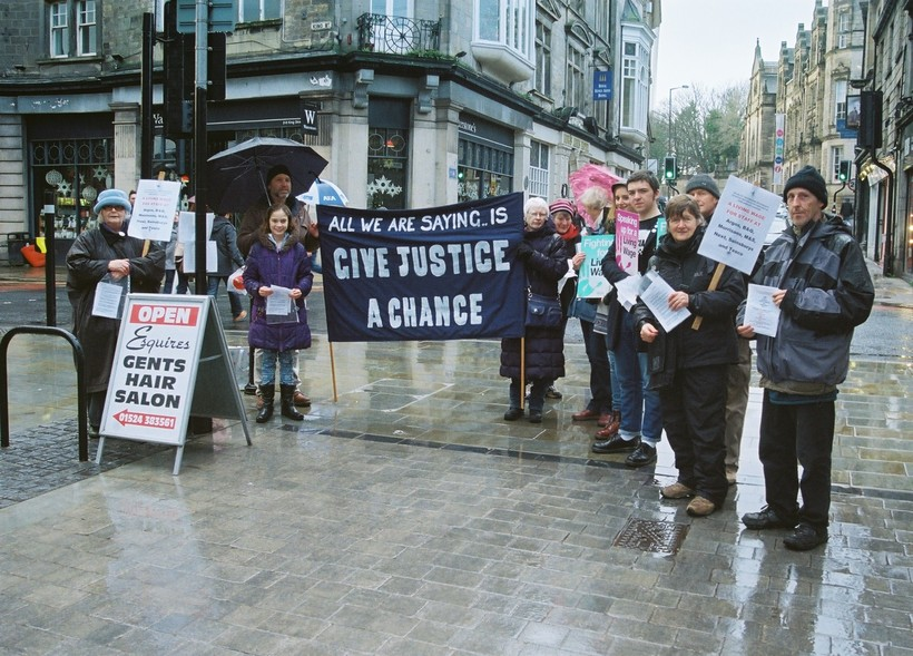 Quakers standing in High Street with flyers about inequality