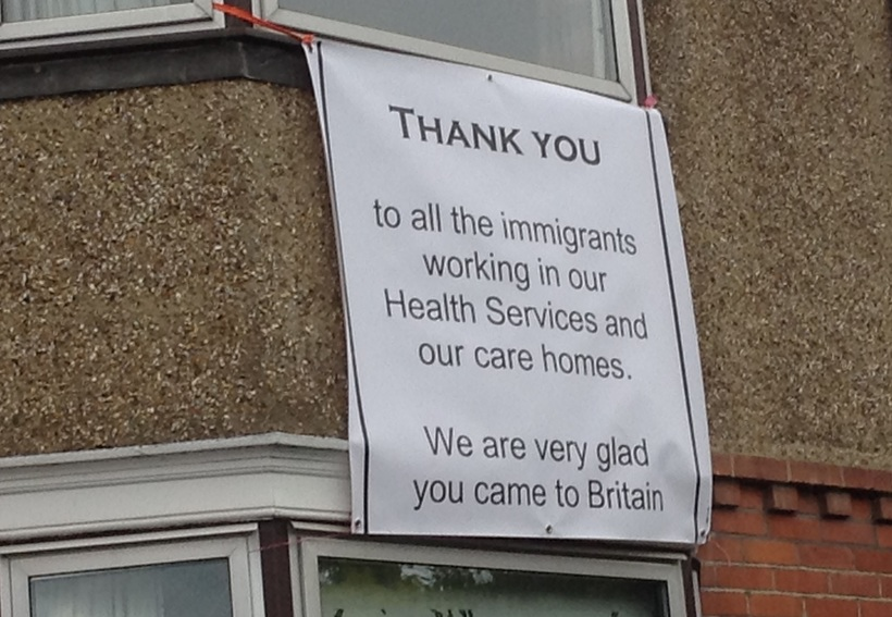 Banner saying thank you to all the immigrants working in our health services and our care homes. We are very glad you came to Britain.
