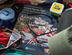 The brochure for Armed Forces Day in Guidlford surrounded by sunglasses and assorted items for a day out.