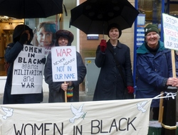 Four women in black and navy standing in the rain with black umbrellas holding a vigil for peace