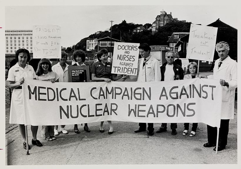 "A group of doctors and nurses hold up a ""Medical Campaign Against Nuclear Weapons"" banner and placards"