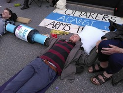 Sam Donaldson lies on the road outside Atomic Weapons Establishment, Burghfield, connected to other protesters