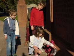 Four children lay a wreath of red and white poppies a tthe foot of the Cavell memorial