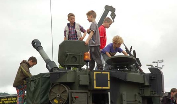 children clamber over military tank
