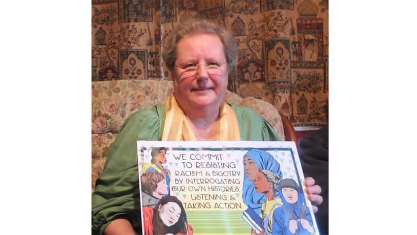 Maria Haines holding a poster from AFSC with the words 'we commit to resisting racism and bigotry by interrogating our own histories, listening and taking action'