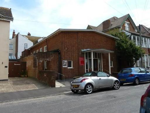Large brick building with column-flanked entrance and red sign reading 'Quaker Meeting House'.