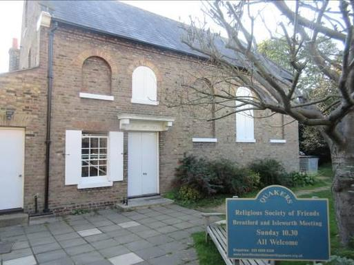 Converted brick house with filled-in arched windows which flank a large white door. A blue 'Quakers Religious Society of Friends' sign stands in the garden grounds.