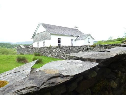 White cottage with long period windows surrounded by stone wall, set within isolated field landscape.