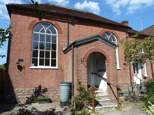 Small brick chapel with large arched windows and decorative entrance porch.