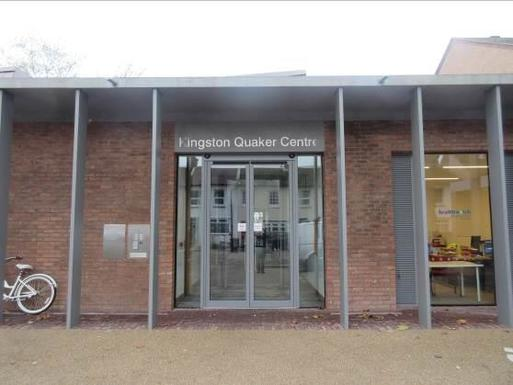 Brick building with grey pillars and glass double door entrance, above which reads 'Kingston Quaker Centre'