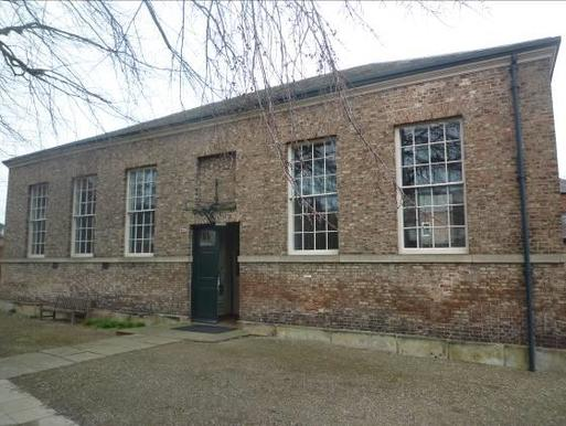 Large brick meeting house with massive windows and walled burial ground on premises.