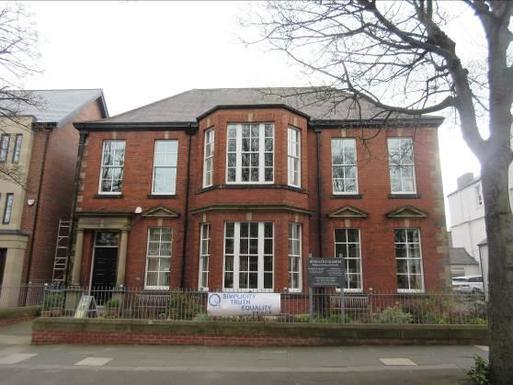 Red brick and ashlar design building with many windows.