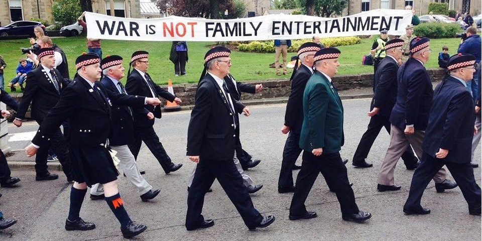 Veterans parading past a banner which says 'War is not family entertainment'
