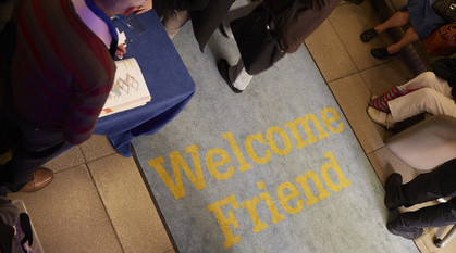 People walking over a mat with the words 'Welcome Friend' written on the mat