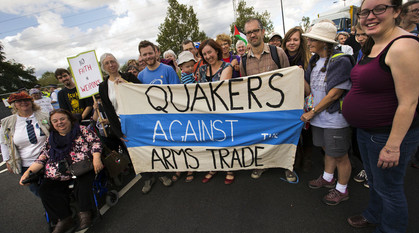 A group of Quakers standing and sitting around a banner with the words 'Quakers Against the Arms Trade' on it.