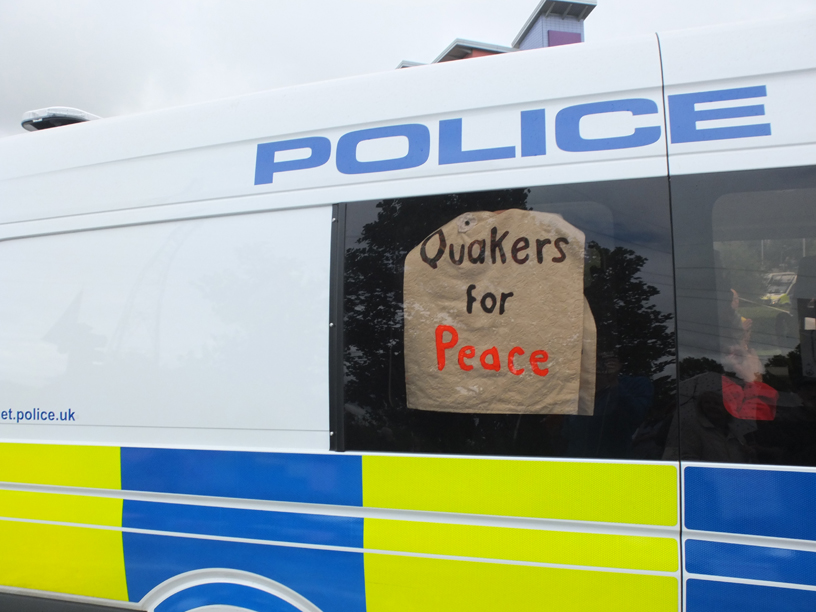 sign in police van window says Quakers for peace