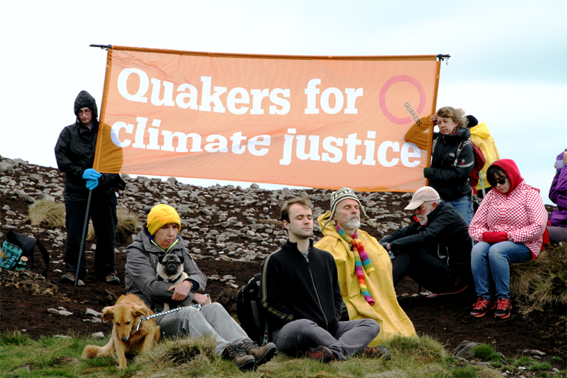 Atop Pendle Hill, activist mfw under orange Quakers for climate justice banner