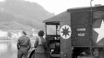 A black and white photograph of a man and woman by a Quaker Relief van