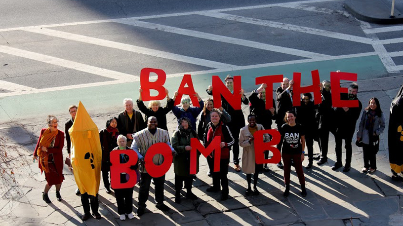 people hold red letters saying ban the bomb