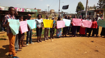 A group of people standing outside in the sunshine holding placards calling for nonviolence during elections in Kenya