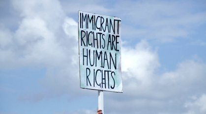 A demonstration holds a placard which reads 'immigrant rights are human rights'