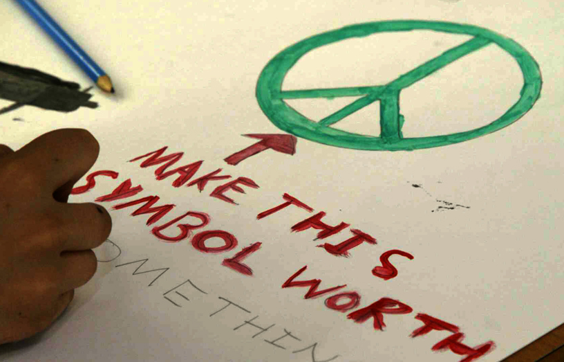 The CND symbol (or peace symbol) being drawn by child with the words 'make this symbol worth something' underneath