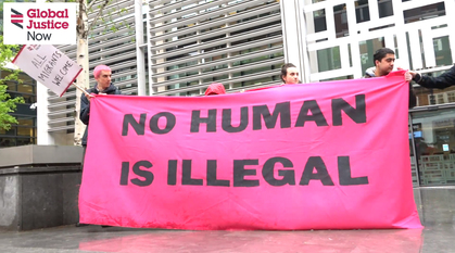 5 people holding up a bright pink banner outside on a grey day with 'No Human Is Illegal' on it.