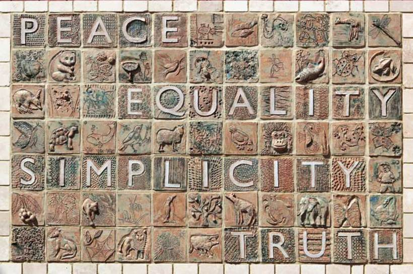 A mosaic in light brown colours includes the words peace, justice, equality and simplicity.