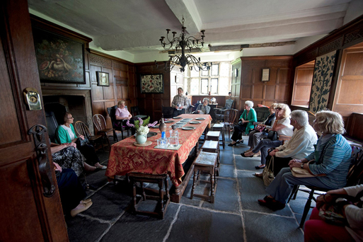 Group of people in a circle in an old room with seventeenth century furniture