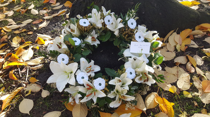 wreath of white flowers including lilies and paper white poppies