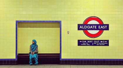 Woman sitting in Aldgate Tube station.