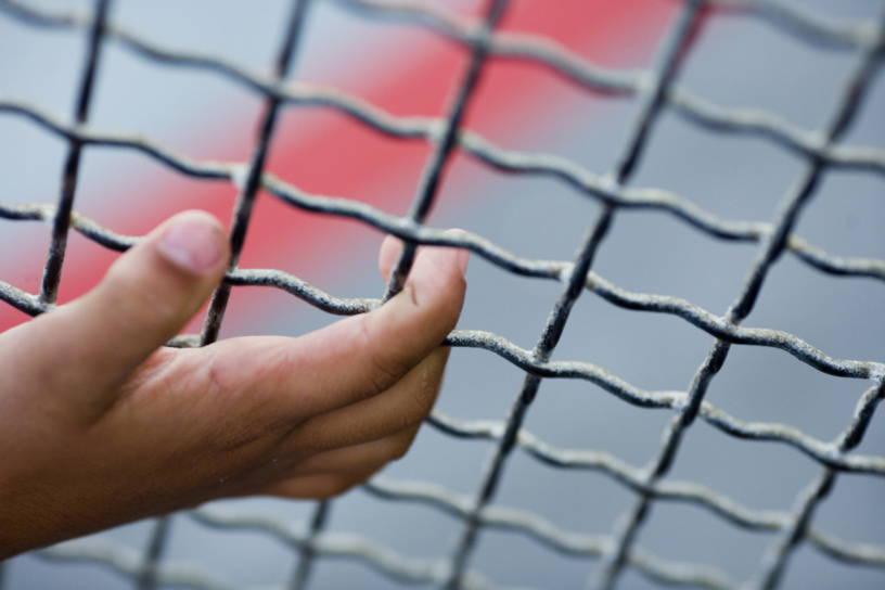 child's hand clings to wire fence
