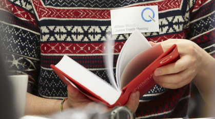 Young person wearing a woolly jumper flicking through red book