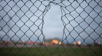 a small hole in chain link fence leading to an unclear and murky field beyond