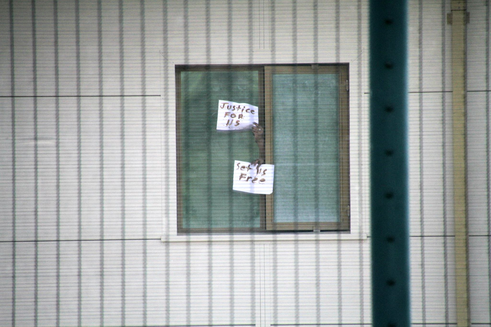 two hands coming out of a window of an immigration detention centre holding up pieces of paper with the words 'justice for us' 'set us free' written on it