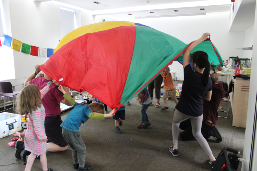 children in red/yellow/blue parachute