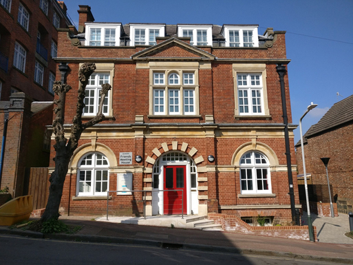 Red brick building with a red door and large windows.