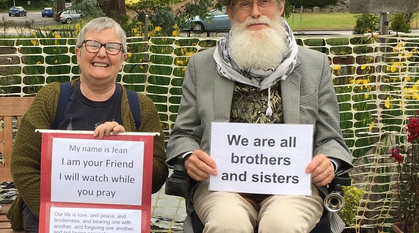 woman sat on a bench smiling and man with long beard and a hat in a wheelchair