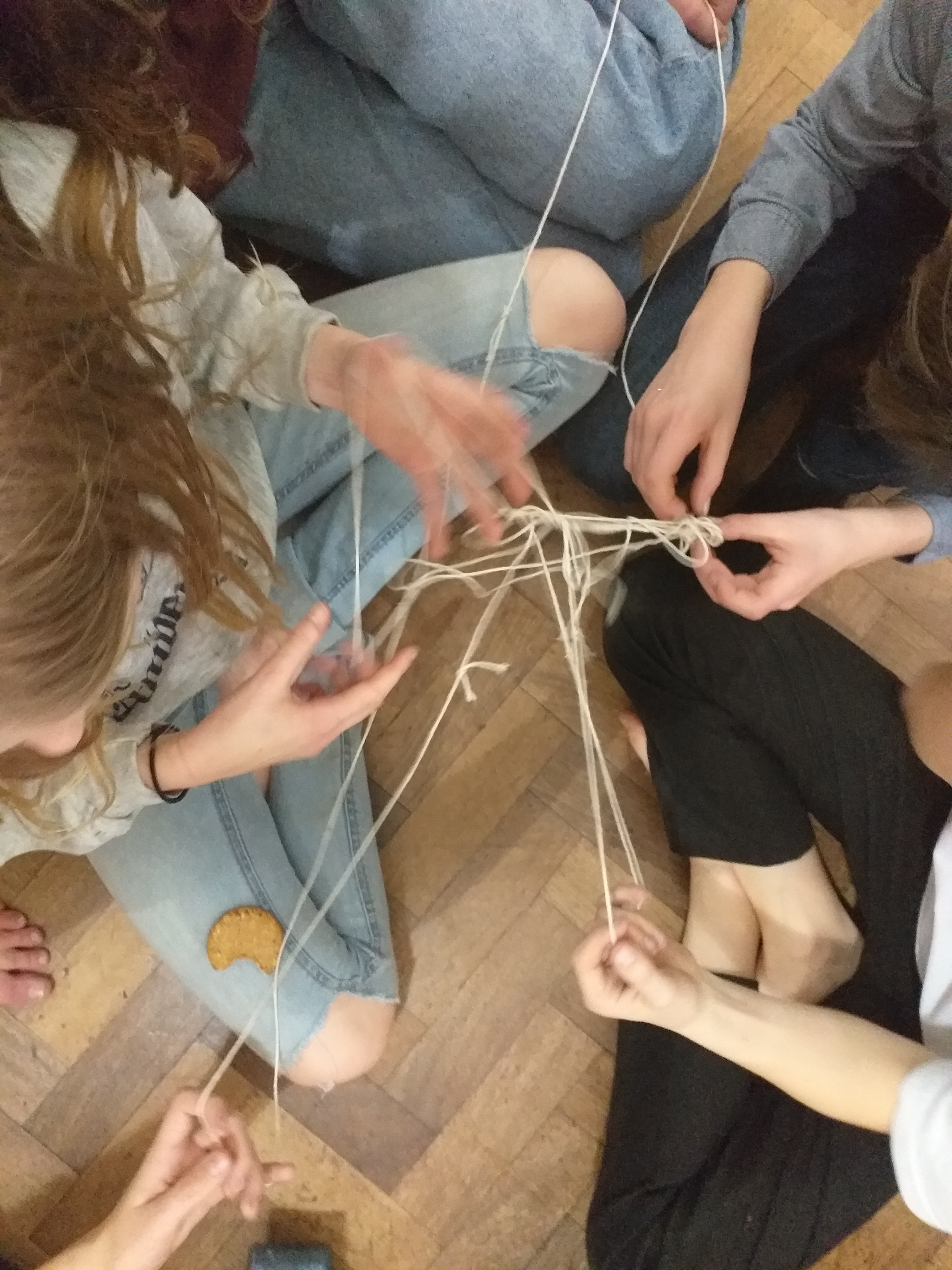 young people playing a game with string